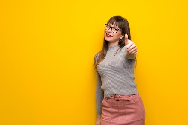 Frau mit brille geben daumen hoch geste, weil etwas gutes passiert ist Premium Fotos