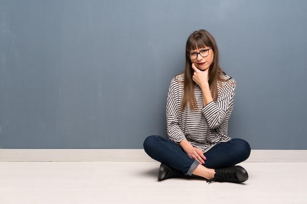 Frau mit brille sitzen auf dem boden denken Premium Fotos