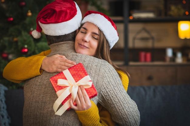 Frau mit dem geschenk, das mann umarmt Kostenlose Fotos