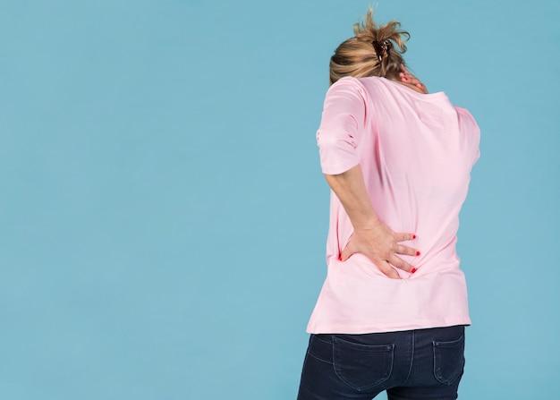Frau mit dem hals und rückenschmerzen, die vor blauem hintergrund stehen Kostenlose Fotos