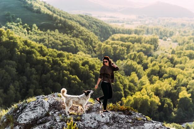 Frau mit dem hund, der in die berge geht. hundefreund. gehen sie mit ihrem haustier spazieren. mit einem hund unterwegs. ein haustier. schlauer hund. Premium Fotos