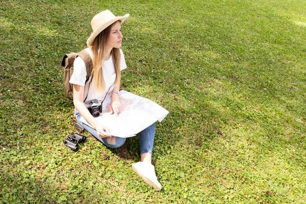 Frau mit dem hut, der auf gras sitzt und weg schaut Kostenlose Fotos