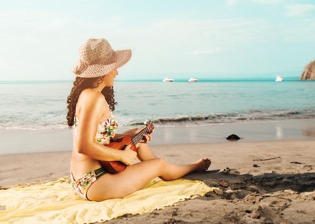 Frau mit dem hut, der ukulele auf sandigem strand spielt Kostenlose Fotos