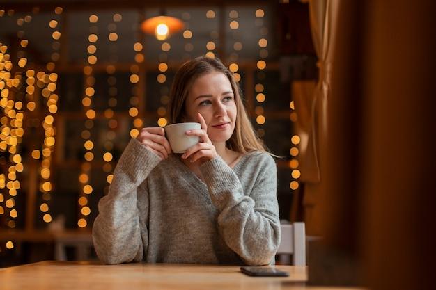 Frau mit dem kaffee, der auf fenster schaut Kostenlose Fotos