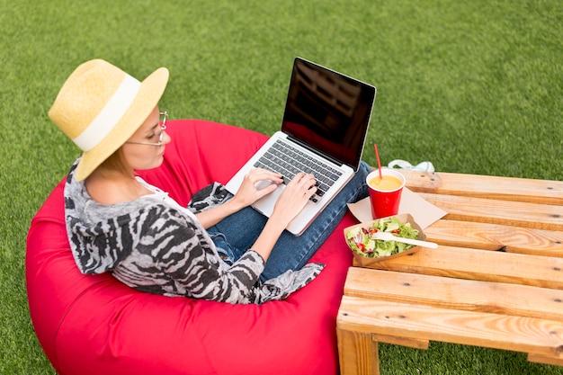 Frau mit dem laptop, der salat betrachtet Kostenlose Fotos
