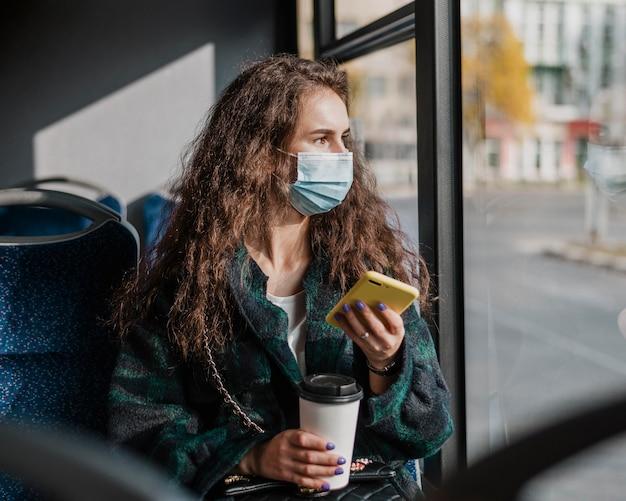 Frau mit dem lockigen haar, das handy und kaffee hält Kostenlose Fotos