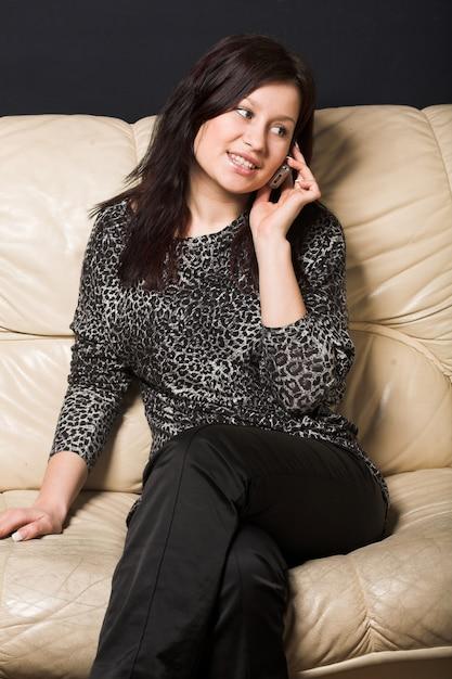 Frau mit dem mobile, das auf sofa sitzt Premium Fotos