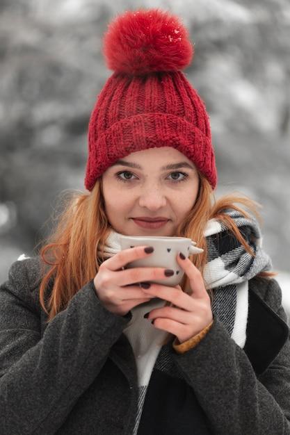 Frau mit dem roten hut, der eine tasse tee hält Kostenlose Fotos