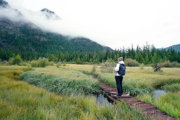 Frau mit dem rucksack, der in forest mountains wandert. Premium Fotos
