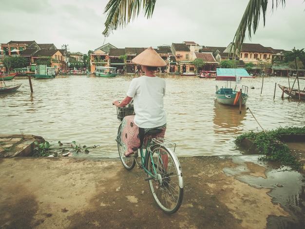 Frau mit dem traditionellen vietnamesischen hut, der auf die flussbank in hoi radfährt. Premium Fotos