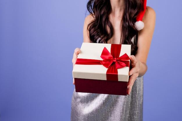 Frau mit dem tragenden weihnachtshut der geschenkbox lokalisiert über purpur Premium Fotos