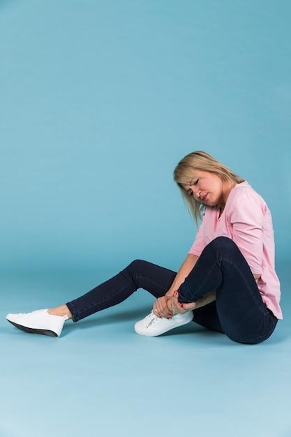 Frau mit dem verletzten fuß, der auf blauem hintergrund sitzt Kostenlose Fotos