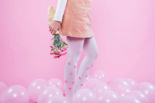 Frau mit den blumen, die auf boden mit ballonen stehen Kostenlose Fotos