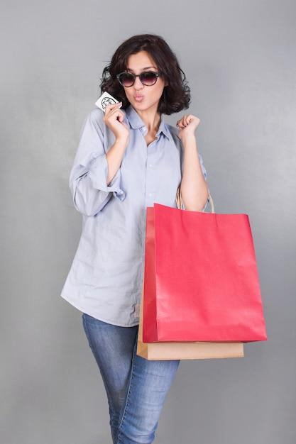 Frau mit den einkaufstaschen, die luft küssen lassen Kostenlose Fotos