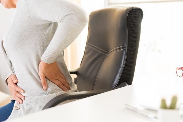 Frau mit den händen, die ihre rückenschmerzen halten. office-syndrom und gesundheits-konzept. Premium Fotos