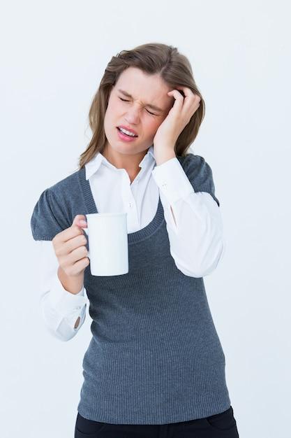 Frau mit den kopfschmerzen, die becher auf weißem hintergrund halten Premium Fotos
