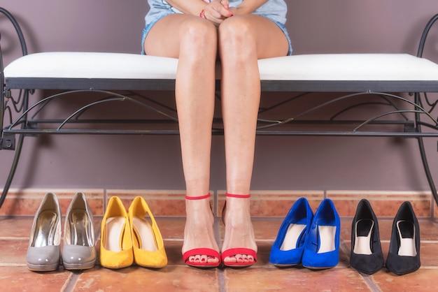 Frau mit den vollkommenen dünnen beinen, versuchend auf verschiedenen schuhen des hohen absatzes. einkaufskonzept Premium Fotos