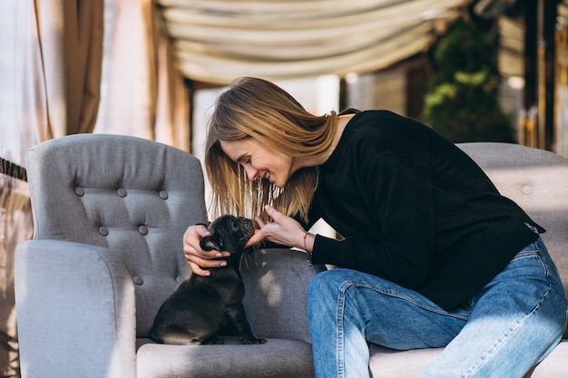 Frau mit der bulldogge, die in einem café sitzt Kostenlose Fotos