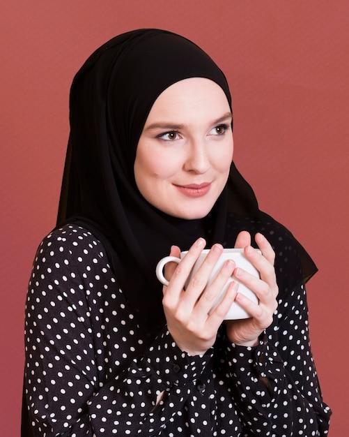 Frau mit der headcover, die weg schaut, kaffeetasse über dunkler oberfläche halten Premium Fotos