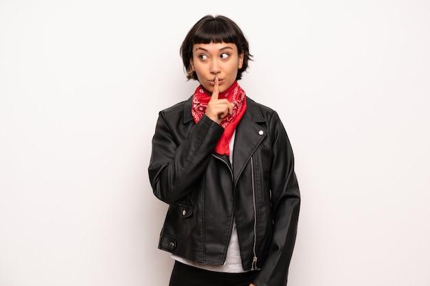 Frau mit der lederjacke und taschentuch, die ein zeichen der ruhegeste zeigen Premium Fotos