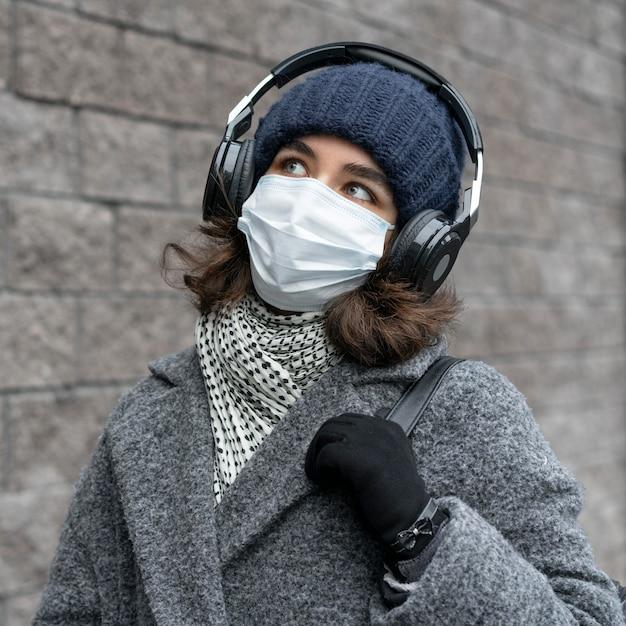Frau mit der medizinischen maske in der stadt, die musik hört Kostenlose Fotos