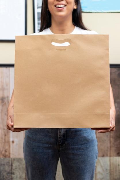 Frau mit der papiertüte, bereit zur lieferung Premium Fotos