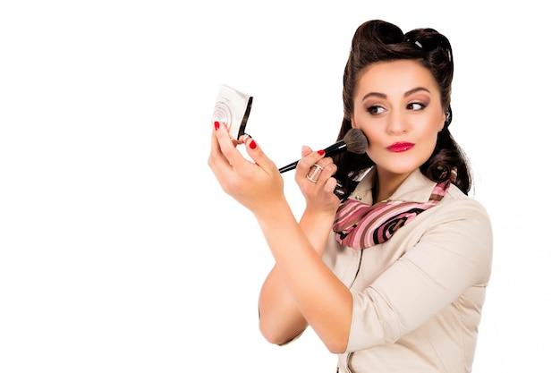 Frau mit der pin-up-frisur, die spiegel hält Premium Fotos