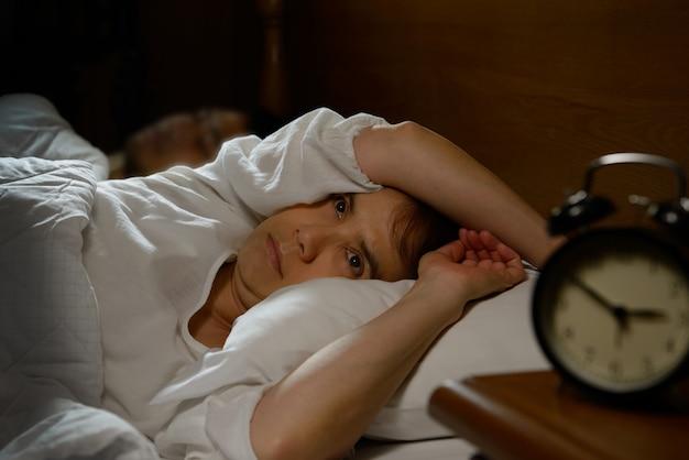 Frau mit der schlaflosigkeit, die im bett mit offenen augen liegt Premium Fotos