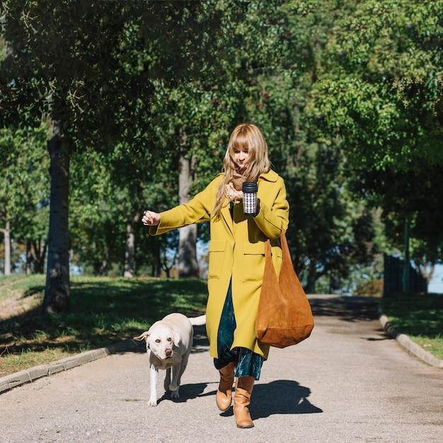 Frau mit der Thermosflasche, die mit Hund geht Kostenlose Fotos