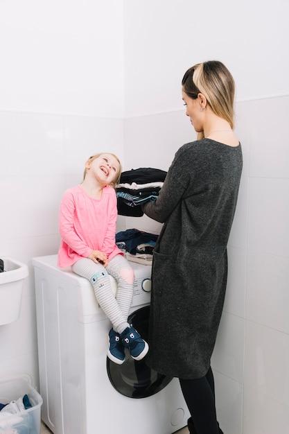 Frau mit der wäscherei, die ihre nette tochter sitzt auf waschmaschine betrachtet Kostenlose Fotos