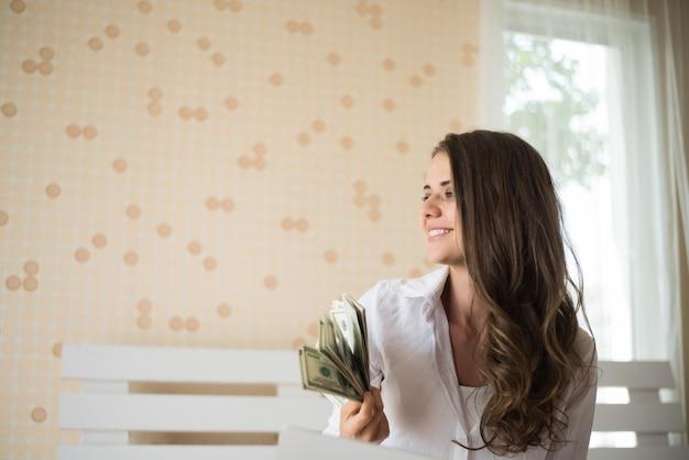 Frau mit dollarbanknote auf dem bett Kostenlose Fotos
