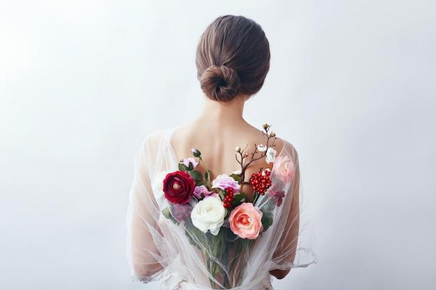 Frau mit einem blumenstrauß von künstlichen blumen hinten Premium Fotos