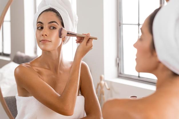 Frau mit einem make-up pinsel Premium Fotos