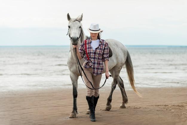 Frau mit einem pferd am strand spazieren Kostenlose Fotos