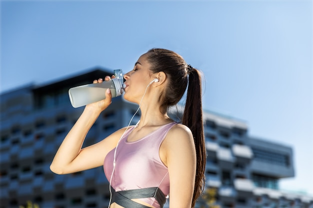 Frau mit einem pferdeschwanz trinkt von der sportiven flasche in den kopfhörern nahe dem modernen gebäude Kostenlose Fotos