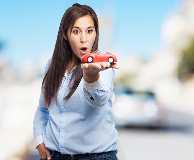 Frau mit einem roten spielzeugauto mit unscharfen hintergrund Kostenlose Fotos