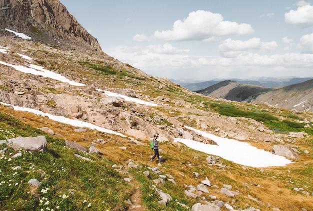 Frau mit einem rucksack, der tagsüber einen berg unter einem bewölkten himmel wandert Kostenlose Fotos