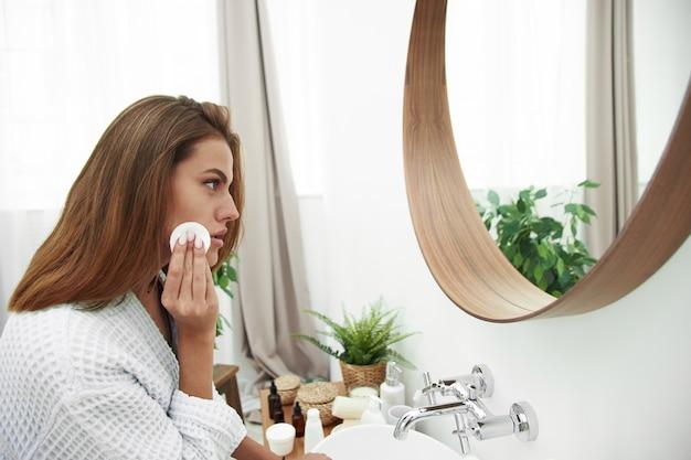 Frau mit einem schwammwattepad problemhaut. ein bild eines glücklichen mädchens, das ihr gesicht mit wattepads über badezimmer säubert. schönes gesicht der jungen frau mit sauberer frischer haut. Premium Fotos