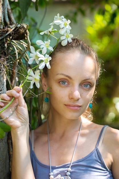 Frau mit einem zweig einer weißen orchidee Premium Fotos