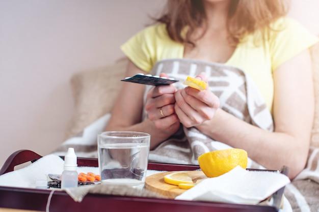 Frau mit einer erkältung wählt zwischen pillen und vitaminen für die behandlung Premium Fotos
