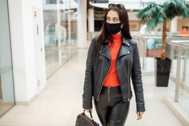 Frau mit einer medizinischen schwarzen maske geht entlang eines einkaufszentrums. coronavirus pandemie. frau in einer schutzmaske kauft im einkaufszentrum ein Premium Fotos