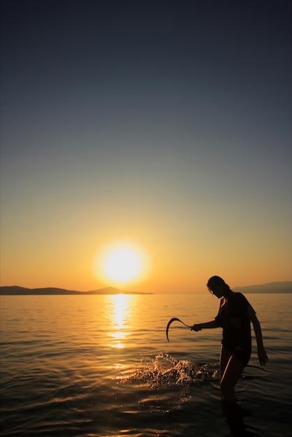 Frau mit einer sichel am strand bei sonnenuntergang Kostenlose Fotos