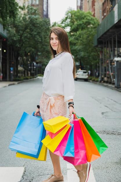 Frau mit einkaufstaschen auf der straße Kostenlose Fotos