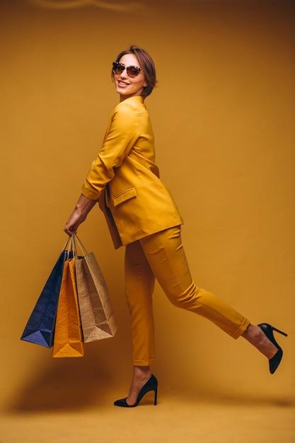 Frau mit einkaufstaschen im studio auf dem gelben hintergrund lokalisiert Kostenlose Fotos