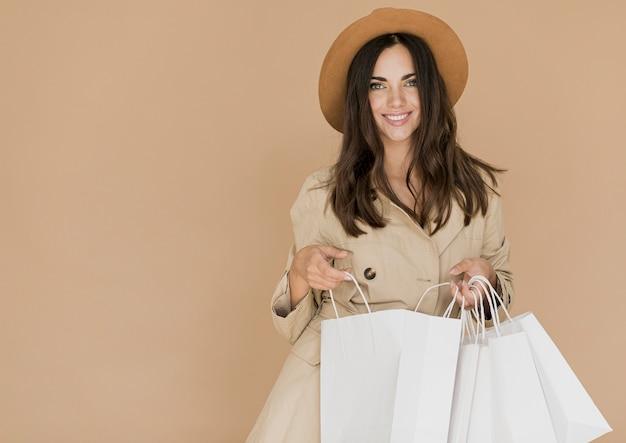 Frau mit einkaufstüten in die kamera schaut Kostenlose Fotos