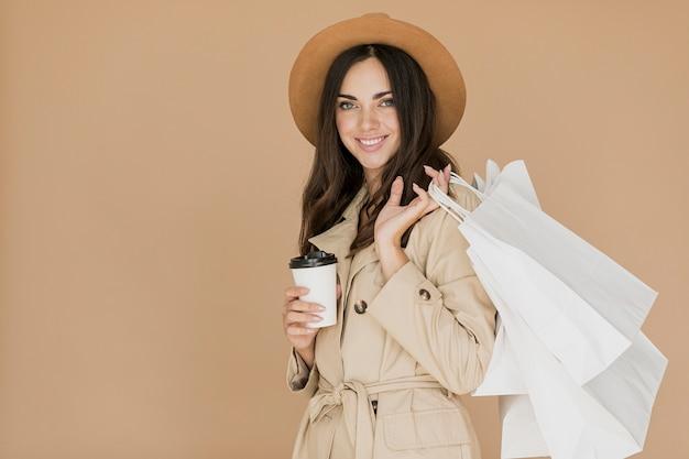 Frau mit einkaufstüten und kaffee lächelnd in die kamera Kostenlose Fotos