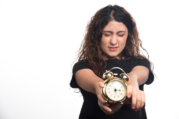 Frau mit engen augen, die einen wecker auf weißem hintergrund zeigen Kostenlose Fotos