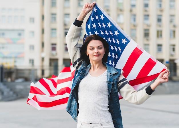 Frau mit flagge der vereinigten staaten auf der straße Kostenlose Fotos