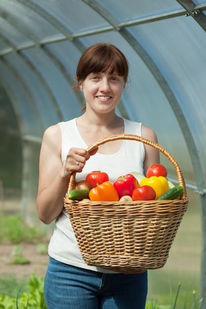Frau mit geerntetem gemüse im gewächshaus Kostenlose Fotos