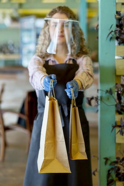 Frau mit gesichtsschutz bei kundenauftrag Kostenlose Fotos